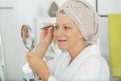 Free Senior Woman Plucking Eyebrows Royalty Free Stock Image - 172607566