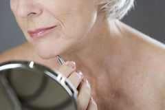 A senior woman plucking hairs from her chin with tweezers stock photos