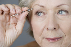 A senior woman plucking her eyebrows with tweezers Royalty Free Stock Photography