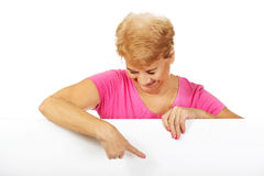 Senior woman pointing for something on empty banner Stock Photo