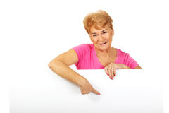 Senior woman pointing for something on empty banner Royalty Free Stock Image