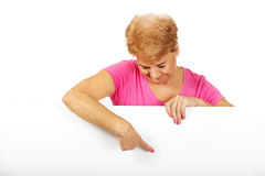 Senior woman pointing for something on empty banner Royalty Free Stock Photography