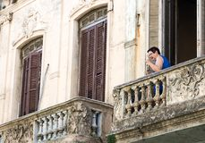 Senior woman pointing up with her finger. Montevideo, Uruguay - February 25th, 2018: A senior woman pointing up from the balcony of her home at the downtown of Royalty Free Stock Photos