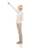 Senior woman pointing up Stock Photo