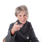 Senior woman pointing at the viewer. Attractive grey haired senior woman sitting in a chair pointing at the viewer identifying a particular person, making a Stock Images