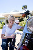 Senior woman polishing motorbike on driveway, crouching down, senior man serving drinks on background, smiling, portrait Stock Image