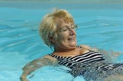 Senior woman in pool. Senior woman has fun in the pool while aqua gymnasics for health stock image