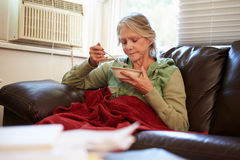 Senior Woman With Poor Diet Keeping Warm Under Blanket. Senior Woman With Poor Diet Keeping Warm Under Red Blanket Looking Unhappy Royalty Free Stock Photos