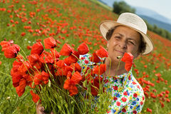 Senior woman on poppy field Stock Images