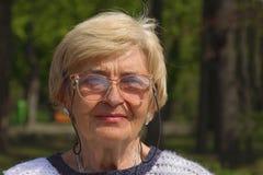 Senior woman portrait. Outdoor portrait of a senior woman with glasses Stock Photos