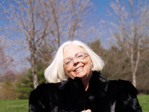 Senior woman portrait. Outdoor portrait of a cheerful senior woman wearing a black fur coat, spring trees in the background Stock Images
