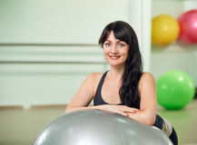 Senior Woman portrait on ball. Portrait of middle-aged woman in a gym looking at camera in a fitness club Royalty Free Stock Photo