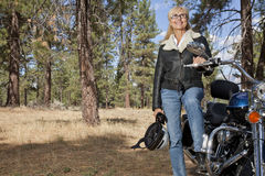 Senior woman poses with motorcycle in forest stock photo