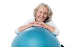 Senior woman posing with exercise ball. Smiling fit aged lady with exercise ball Royalty Free Stock Image
