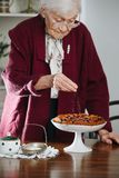 Senior woman pouring powdered sugar on tasty holiday pie on a table. Senior gray haired woman pouring powdered sugar on tasty holiday pie on a dinner table at royalty free stock image