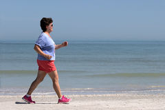Senior woman power walking on a beach. Royalty Free Stock Photo