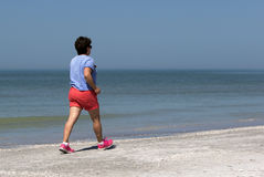 Senior woman power walking on a beach. Stock Photo