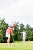 Senior woman practicing with golf pro Royalty Free Stock Photography