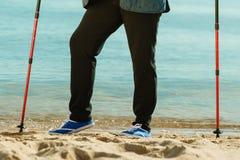 Senior woman practicing nordic walking on beach Stock Image