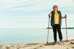 Senior woman practicing nordic walking on beach Stock Photos