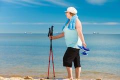 Senior woman practicing nordic walking on beach Stock Images