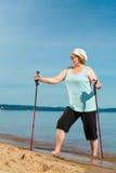 Senior woman practicing nordic walking on beach Royalty Free Stock Image