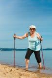 Senior woman practicing nordic walking on beach Royalty Free Stock Photo