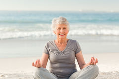 Senior woman practicing yoga on the beach Stock Image