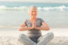 Senior woman practicing yoga on the beach royalty free stock photos