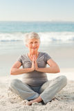 Senior woman practicing yoga on the beach Stock Photography
