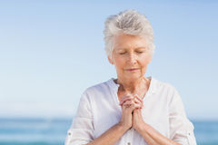 Senior woman praying on the beach Royalty Free Stock Photography