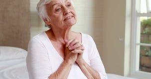 Senior woman praying in bed stock video