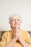 Senior woman praying / doing meditation Stock Photo