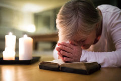 Senior woman praying, hands clasped together on her Bible. Senior woman kneeling on the floor praying with hands clasped together on her Bible. Burning candles Royalty Free Stock Photos