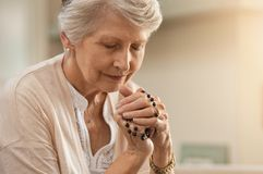 Senior woman praying. While holding christian symbol of crucifix. Old woman praying to god with hope and closed eyes. Elderly believer make a prayer with faith stock photography