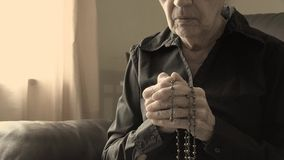 Senior woman praying and holding a rosary or crucifix in her old hands stock video footage