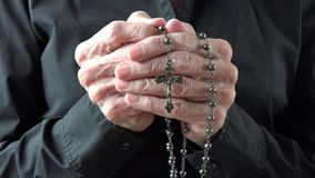 Senior woman praying and holding a rosary or crucifix in her old hands stock footage