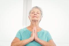 Senior woman praying at home Stock Photos