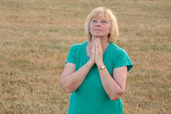 Senior woman praying outside. A mature woman with hands folded, looking up, outdoors stock images