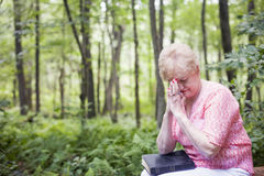 Senior woman praying. A senior woman sitting in a forest with a bible in prayer stock image
