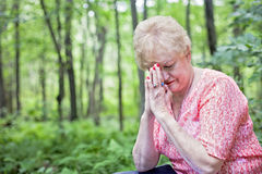 Senior woman praying. A senior woman sitting in a forest with a bible in prayer royalty free stock images