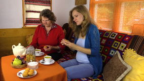 Senior woman and pregnant granddaughter eat sweets with tea stock video