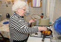 Senior woman prepares food Royalty Free Stock Images