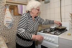 Senior woman prepares food Stock Photo
