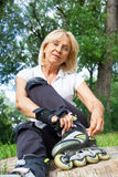 Senior woman prepares for roller skating Stock Photo