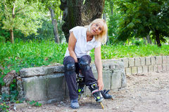 Senior woman prepares for roller skating Royalty Free Stock Photography