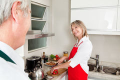 Senior woman preparing dinner Royalty Free Stock Photos