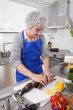 Senior woman preparing fish in kitchen Stock Photos