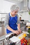 Senior woman preparing fish in kitchen Stock Photos