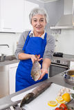 Senior woman preparing fish in kitchen Royalty Free Stock Photos